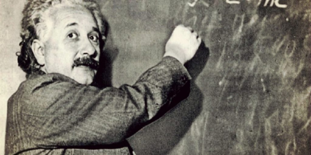 Albert Einstein writing on blackboard