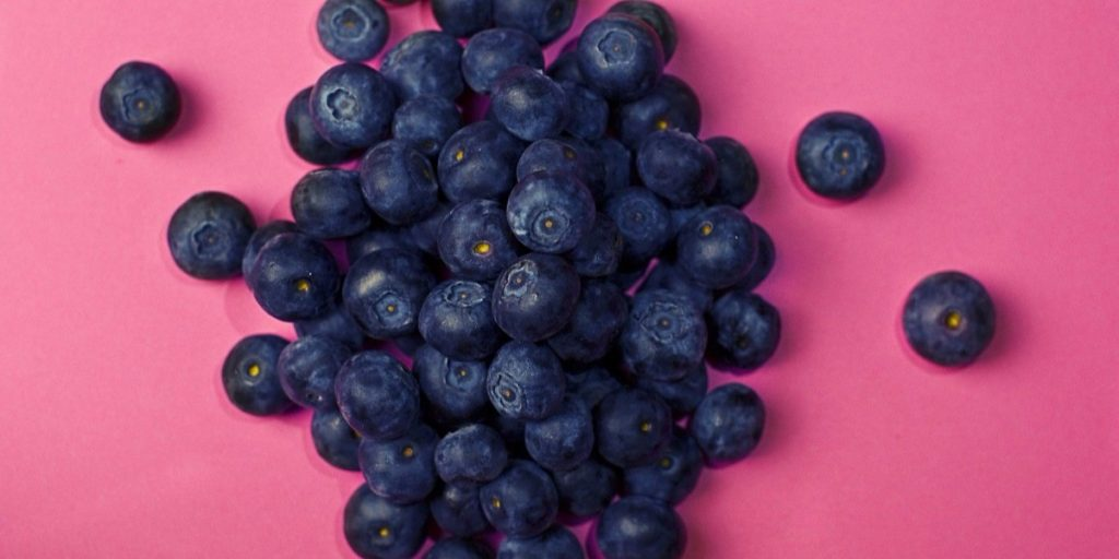 A handful of blueberries on a pink background.