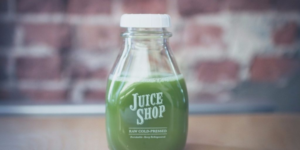 A small glass bottle filled 3/4 full with Juice Shop brand raw cold pressed green juice on a wooden table with brick background