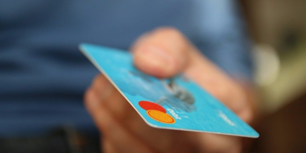 Man presenting a sky blue debit card to pay for an item.