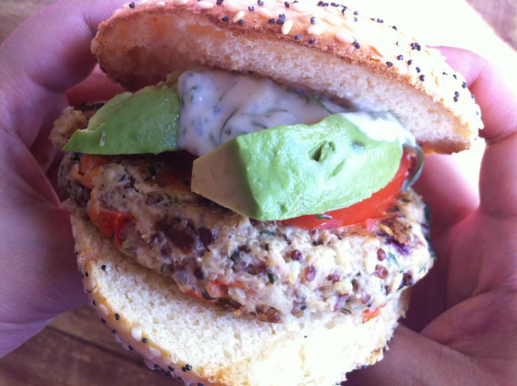 Tangy Tuna Burger Recipe Without Breadcrumbs. Person holding a tuna burger in their hands about to eat it. The tuna burger is topped with tzakiki sauce, avocado, and tomato.
