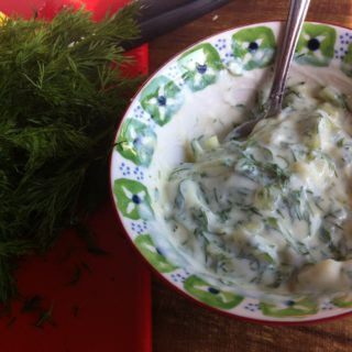 A small bowl of tzatziki sauce (gluten free) with a bunch of fresh dill on the left.