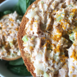 tuna salad with apples and celery on a gluten free bagel