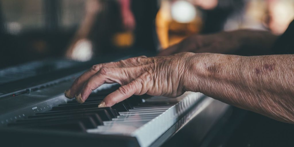 Aged hands playing the piano.
