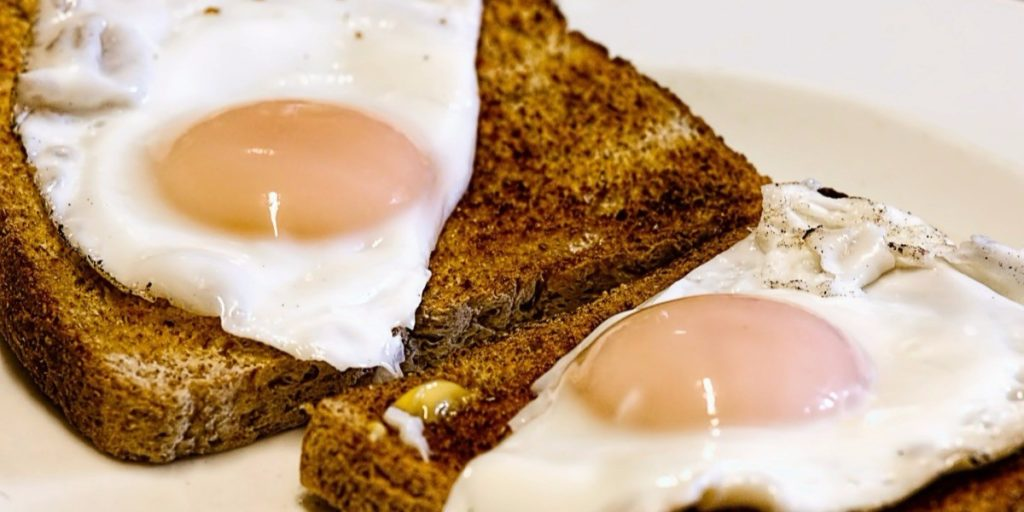 Two sunny side up eggs on two slices of whole wheat toast.
