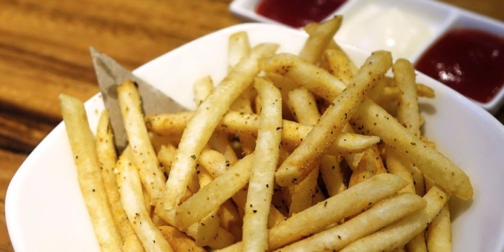 Fries on a plate with three dipping sauces on the side.