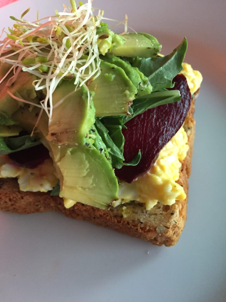 Open egg salad beet sandwich.