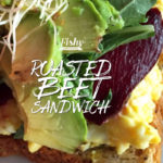 close up image of a sandwich with roasted beets, avocado, scrambled eggs, arugula, sprouts